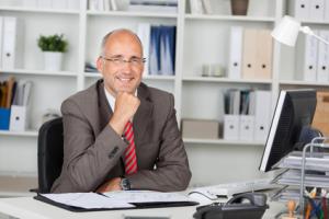 Businessplan Berater sitzt am Schreibtisch